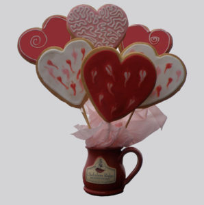 Heart cookies on skewers to make a cookie bouquet in a red mug with the Chehalem Ridge B&B logo on it